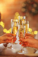 Champagne glasses in hands on golden background