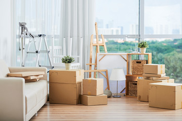Spacious interior with large packed carton boxed for moving on floor with sofa and drawing easels nearby at large glass wall on sunny day Wall mural