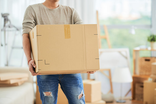 Crop view of strong male in casual clothes carrying large cardboard box on moving day with cartons and drawing easels on blurred background of art workshop.
