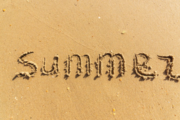 Summer - the word drawn on a yelow wet sand.
