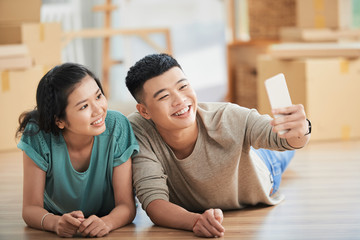 Happy young Asian couple lying on floor of new apartment on moving day and taking picture on smartphone front camera smiling on blurred background