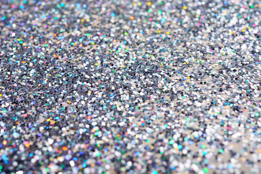 Abstraction of bright glowing silver glitters in heap shimmering and blinking in lights