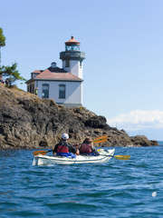 Couple in a sea kayak and lighthouse