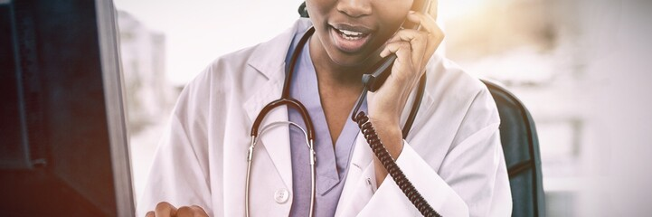 Female doctor on phone while using computer