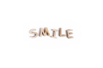 Word Smile made of wooden letters on a white background