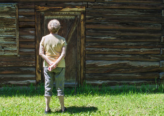 rear view of middle aged Caucasian woman standing in the grass looking at the closed wooden door of a weathered antique barn with copy space