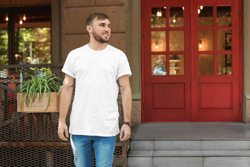 Young man wearing white t-shirt on street