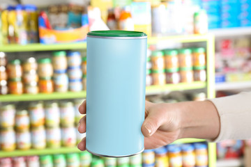 Woman holding can with baby milk formula in store
