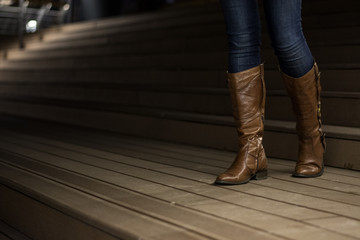 Young girl in leather boots walking down the stairs