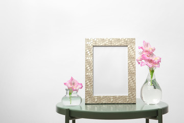 Blank frame and vases with flowers on table against white background. Mock up for design