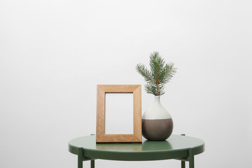 Blank frame and vase with fir branch on table against white background. Mock up for design