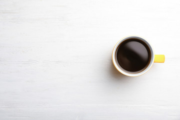 Ceramic cup with hot aromatic coffee on wooden background, top view