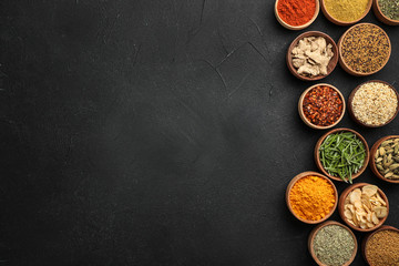 Flat lay composition with different aromatic spices on dark background
