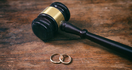 Wedding rings and judge gavel on wooden background, copy space