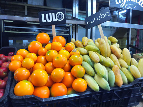 Lulo (Fortunella margarita) and curuba (Passiflora mollissima) tropical Fruits for sale at market stall
