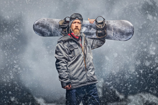 Brutal redhead snowboarder with a full beard in a winter hat and protective glasses dressed in a snowboarding coat posing with a snowboard in a studio, looking at a camera.