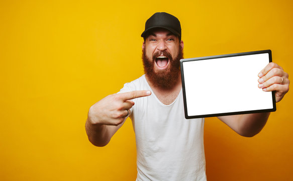 Cheerful amazed happy bearded hipster man in white t-shirt pointing at white screen on tablet at copyspace