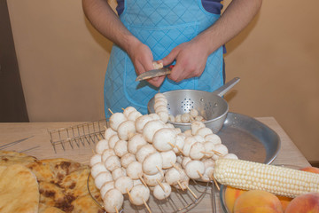 Male hands cuts mushroom with knife, apron on background. Cooking process concept. Cook burgundy uniform cut vegetables