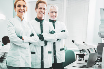 New discovery. Biotechnologists wearing white laboratory uniform feeling very busy while planning new discovery