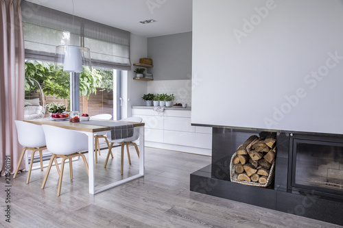 Modern Fireplace And Wood In A Spacious Dining Room Interior With White Chairs By Wooden