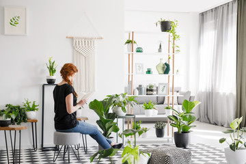 Ginger woman reading a book in a modern living room interior with plants