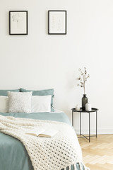Posters above bed with pillows and knit blanket in bright bedroom interior with table. Real photo