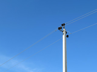 Power line support isolated on blue sky background. Power pole with electrical wires and capacitors, electricity concept