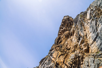Big mountain cliff under cloudy sky close-up. Beautiful rocky gray textured background with vegetation. Majestic nature.