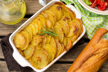 Baked crispy potato slices with rosemary served with salad