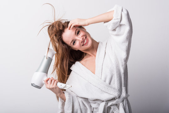 Beautiful red-haired girl in a white bathrobe bathing her hair with a hair dryer on a light background