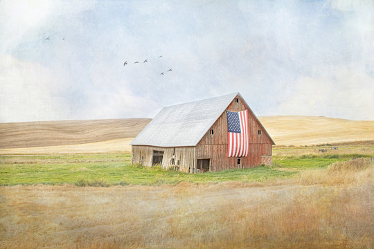 Textured photograph of an old red rickety barn with an American flag on the side