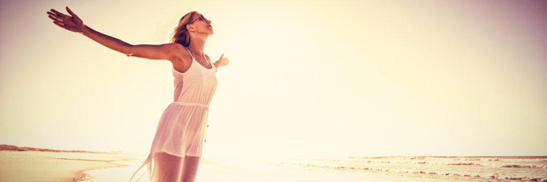 Full length of woman with arms outstretched standing at beach