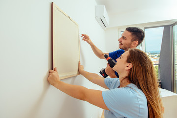Female and her husband are hanging picture together at home. Home renovation concept.