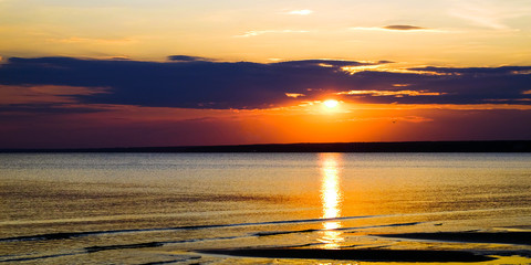 Beautiful blazing scenery of the sunset over the sea and the orange sky above him with amazing Golden reflection of the sun on the calm waves in the background.