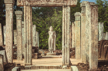 Standing Buddha sculpture and many columns at temple complex from 12th century, Polonnaruwa, Sri Lanka. UNESCO World heritage Site