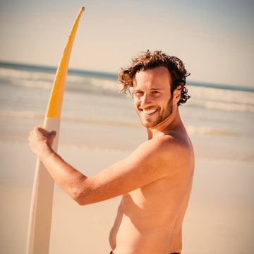 Portrait of happy shirtless man holding surfboard at beach