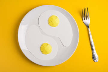 Fond de hotte en verre imprimé Ouf Top view of white plate with paper fried eggs on yellow paper background. Good morning or food art