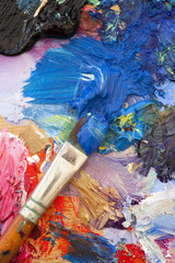 Multi coloured art oil painting palette and brush close up