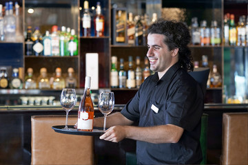 A young men bartender carries a bottle of red wine with wine glasses on a tray to the client of the hote bar, restaurant.  The concept of service.