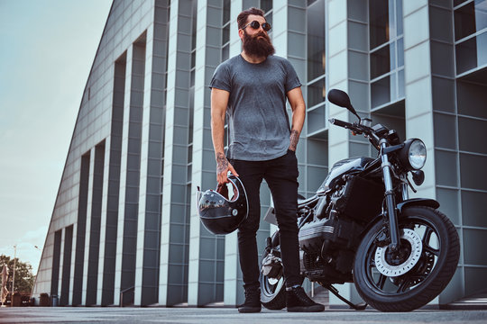 Brutal bearded male in sunglasses dressed in a gray t-shirt and black pants standing near his custom-made retro motorcycle against skyscraper.
