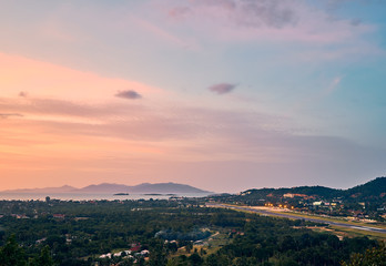 Colourful sunset over airport, mountains and forest on a tropical island