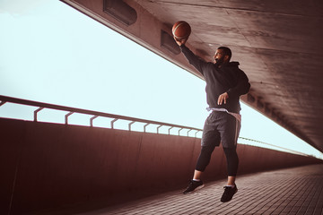 Portrait of a dark-skinned guy dressed in a black hoodie and sports shorts playing basketball on a footway under bridge.