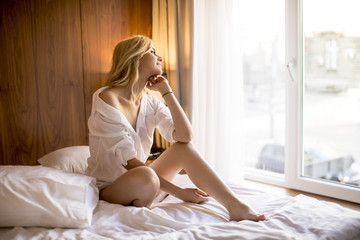 Young woman sitting on the bed at room