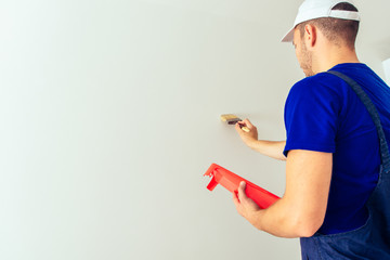 Painter man at work with a paintbrush. Home renovation concept.