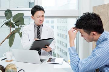 頭痛の患者の症状を聞く医師