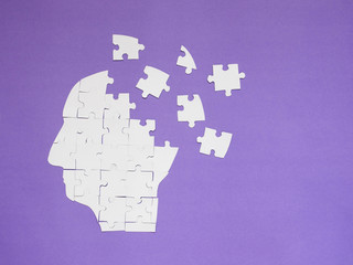 Wall Mural - White jigsaw puzzle as a human brain on purple background w/ copy space. Creative idea for memory loss, Alzheimer's disease, dementia, Parkinson's disease, emotion stress and mental health concept.