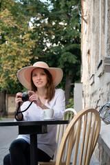 tourist woman digital camera street cafe terrace girl hat sun vintage travel photo shooting white cup coffee panasonic lumix