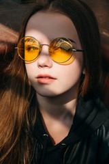 beautiful fashionable teenager girl with long blonde hair in yellow sunglasses in city, Street fashion kid,