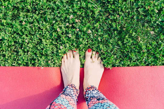 Women's legs with red nails in colored leggings are on a yoga Mat on the grass, on a Sunny summer day. The view from the top, space for text