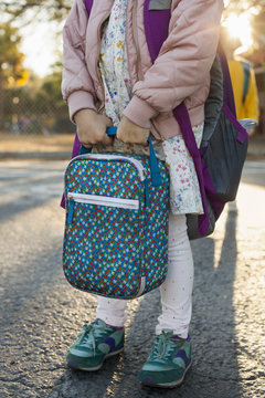 View of a girl holding a lunch box and wearing a back pack outside of school.